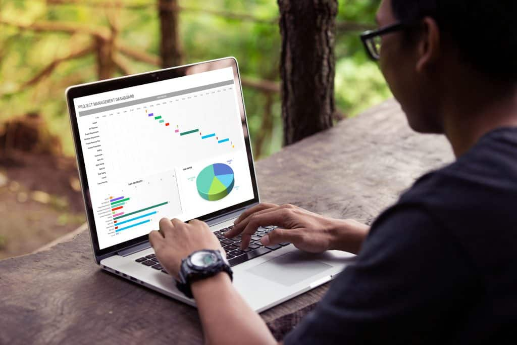 Man working with excel project dashboard on laptop outdoor
